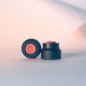 Photo of two black skincare bottles with decorative orange wax seal on top